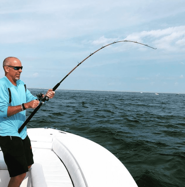 Man fishing the ocean with a fish on the line